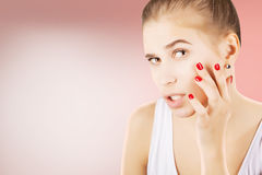 Young girl looking to her skin with astonishment, pink backgroun Royalty Free Stock Photos