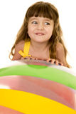 Young girl looking to side over big beach ball Stock Images