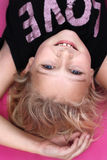 Young girl looking up at the camera. A 9 year old girl lying on the floor, upside down Stock Photography