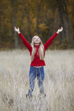 Young Girl Looking Upward. Outdoor photo of pretty young girl standing in field, arms extended upward Stock Photography