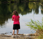 Young Girl looking where to fish on lake Stock Photos