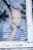 Young girl looking from window Stock Image