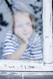 Young girl looking from window Royalty Free Stock Images