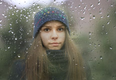 Young girl looking through a window with raindrops. A portrait of a young girl looking through a window with raindrops Stock Photo