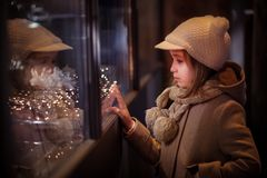 Young girl looking on windows shopping, with illuminated christmas garland. stock image