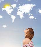 Young girl looking at world clouds and sun on blue sky Stock Photo