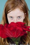 Young girl is looking at you over a big rose Stock Photo