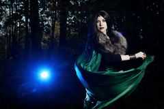 Young girl looks as witch and blows raincoat in dark forest Stock Image