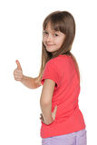 Young girl looks back and holds her thumb up Stock Photography