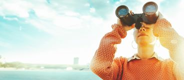 Young girl looks through binoculars at the sea on a bright sunny day. Travel Concept stock photo