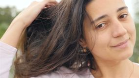 A young girl looks into the camera and straightens her hair. Beautiful smile on her face. Close-up. Slow-motion stock video