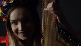 A young girl looks coquettishly at a friend and plays a bandura. The girl looks coquettishly into the camera and fingernails the strings on the bandura stock video footage
