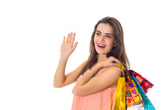 Young girl looks in the direction of the raised hand up and keeps the shoulder bags isolated on white background Stock Photography