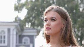 Young girl looks into the distance and correct her hair with her hand. Closeup portrait. Young girl looks into the distance and correct her hair with her hand stock video footage