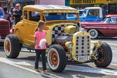 A young girl looks at the engine of a Ford Model A hot rod royalty free stock photo