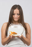 A young girl looks at a goldfish in an aquarium, which holds Royalty Free Stock Image