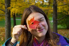 A young girl looks through the hole in the autumn maple leaf Royalty Free Stock Photos