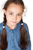 A young girl looks. A young girl with long pigtails looks ahead stock photo