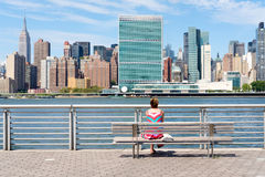 Young girl looks at the Manhattan skyline from a park in Queens. NEW YORK,USA - AUGUST 21,2016 : A young girl looks at the Manhattan skyline from a park in Royalty Free Stock Photo