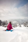 Young girl looks at mountains in winter. Young woman sits on the mountain hillside and looks forward to the skyline view in front of beautiful pine trees in Royalty Free Stock Photos