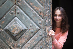 Young  girl looks out from behind the ancient wooden gate. Stock Photography