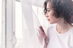 Young girl looking to the window in the morning. The concept of pensive loneliness. stock images