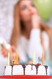 Young girl looks sad on her birthday. Young beautiful blond girl wearing cone cap sitting on a couch and holding a glass of champagne with a birthday cake with Royalty Free Stock Images