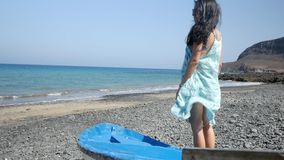 Young girl looks at the sea. Near a fishing boat, pozzo negro fuerteventura stock footage