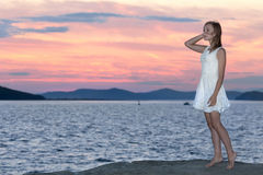 Young girl looks at sunset. At the beach Stock Images
