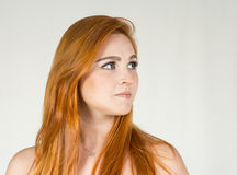Young girl looks to the side. The teenager is white, red-haired Royalty Free Stock Image