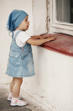 Young girl looks to the window Royalty Free Stock Photo