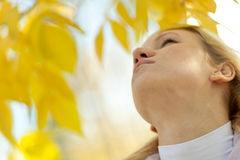 Young girl looks up against yellow leaves Stock Images