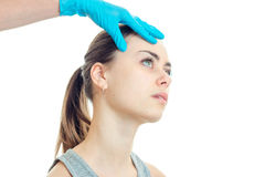 A young girl looks up and cosmetologist verifies a person in a blue glove Stock Photo