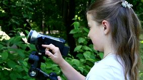 Young girl looks into video camera on background of green park background. stock video