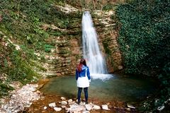 A young girl looks at the waterfall. royalty free stock images