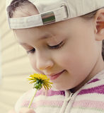 The young girl looks at a yellow flower of a dandelion Stock Images
