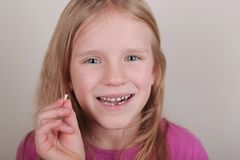 Young girl lost her first bottom front milk teeth. Childhood healthcare concept. Young blond beautiful girl lost her first bottom front milk teeth. Childhood royalty free stock images