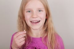 Young girl lost her first bottom front milk teeth. Childhood healthcare concept. Young blond beautiful girl lost her first bottom front milk teeth. Childhood royalty free stock image