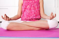 Young girl in lotus position - meditating at home Royalty Free Stock Image