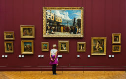 Young girl at the Louvre Museum looking at paintings stock photography