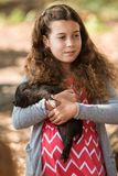 Young Girl Lovingly Holds Sleeping Piglet At Georgia Fall Festival. Alpharetta, GA, USA - September 30, 2017:  A grade school girl lovingly holds a sleeping Royalty Free Stock Image