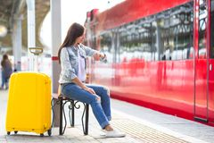 Young girl with luggage on the platform waiting Royalty Free Stock Image