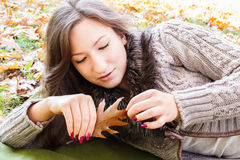 Young girl lying in the autumn leaves at the park Royalty Free Stock Images