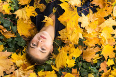 Young  girl lying in the autumn yellow leaves. Royalty Free Stock Images
