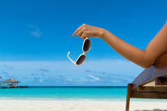 Young girl lying on a beach lounger with glasses in hand Stock Images