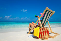 Young girl lying on a beach lounger with glasses in hand on the Royalty Free Stock Image