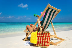 Young girl lying on a beach lounger with glasses in hand on the Royalty Free Stock Photos
