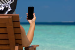 Young girl lying on a beach lounger with mobile phone in hand on Royalty Free Stock Image