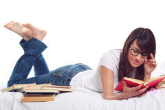 Young girl lying on bed surrounded by books Stock Photography