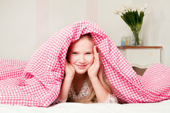 Young girl lying on the bed under the covers. Funny little girl lying on the bed under the covers Royalty Free Stock Photos